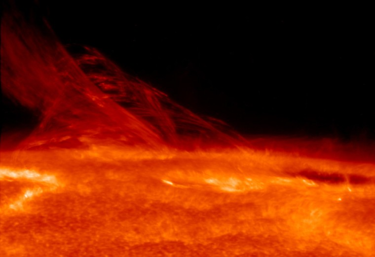 This high-resolution images at the edge of the sun's visible surface was obtained with the Solar Optical Telescope aboard Japan's Hinode satellite. A special filter has been applied to the image to show the brighter photosphere and the fainter coronal structures in the same image.