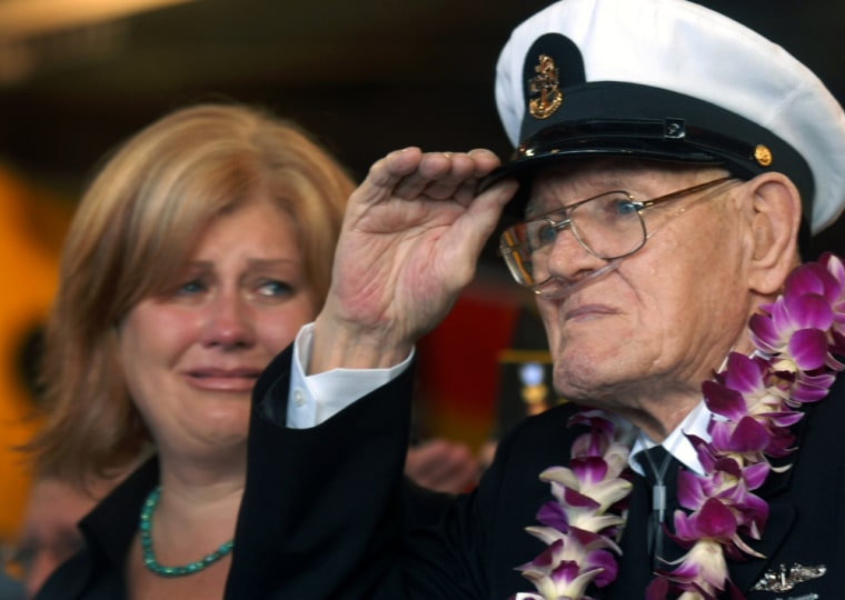 Image: Lois Deininger of San Francisco watches her father, Pearl Harbor survivor, Edward Gaulrapp of Freeport Illinois, salute during the commemoration marking the 66th anniversary of Pearl Harbor attack