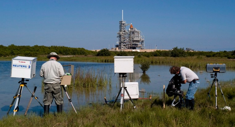 Image: Members of the media once again reset their remote cameras in the swamp area near space Shuttle Atlantis at launch pad 39A