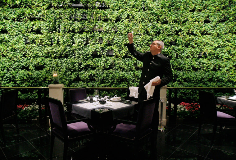 Image: Chef de rang Yann Bousseau sets a table at Joel Robuchon, a Michelin three-star restaurant, at the MGM Grand hotel and casino in Las Vegas