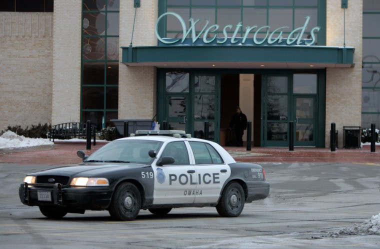 Image: An Omaha police car drives by an entrance to the Westroads Mall.