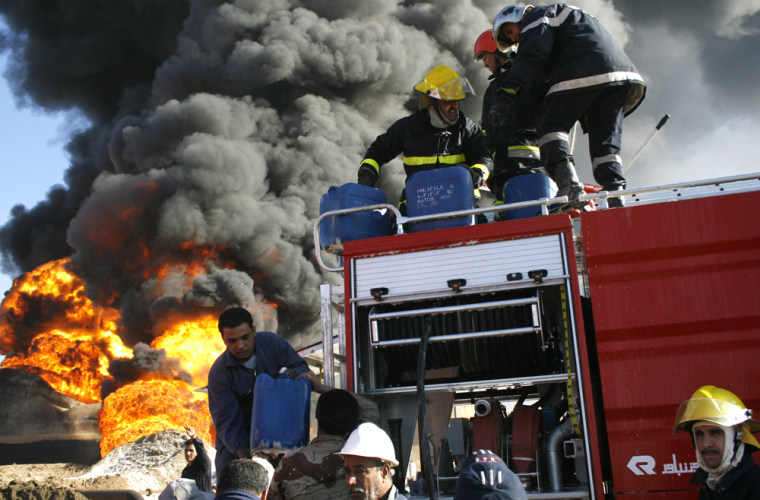 Firemen attempt to extinguish a fire at the al Dora oil refinery Monday in southern Baghdad, Iraq.
