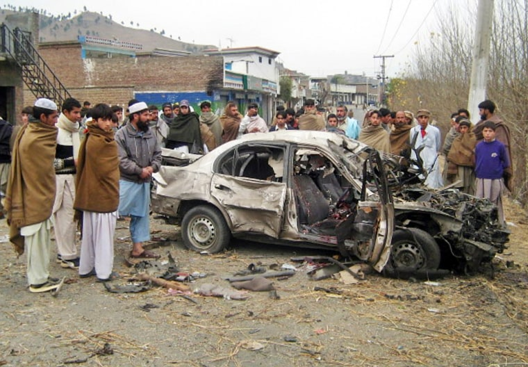 Men stand aroundadamaged car afterasuicide attack on Sundayin theKabal district of Pakistan's Swat valley where the military has launched an operation pro-Taliban militants.