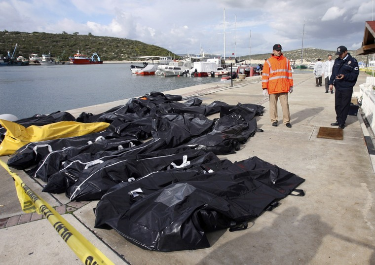 Turkish policeman and a coast guard officer stand next to body bags on Seferihisar port near Izmir