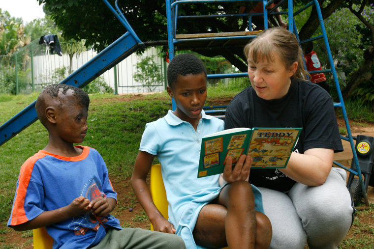 Brownen Jones, right, reads a book with Precious van Wyke, center, and Feleng Mahamotse at the Children of Fire charity in Johannesburg, South Africa, onDec. 6.Jones, the Englishwoman who founded Children of Fire in South Africa, said Chadian authorities are not letting a boy who was thrown into a fire and left to die by janjaweed fighters in Sudan's bedeviled Darfur province travel to South Africa for surgery in fallout from the Zoe's Ark kidnap case.
