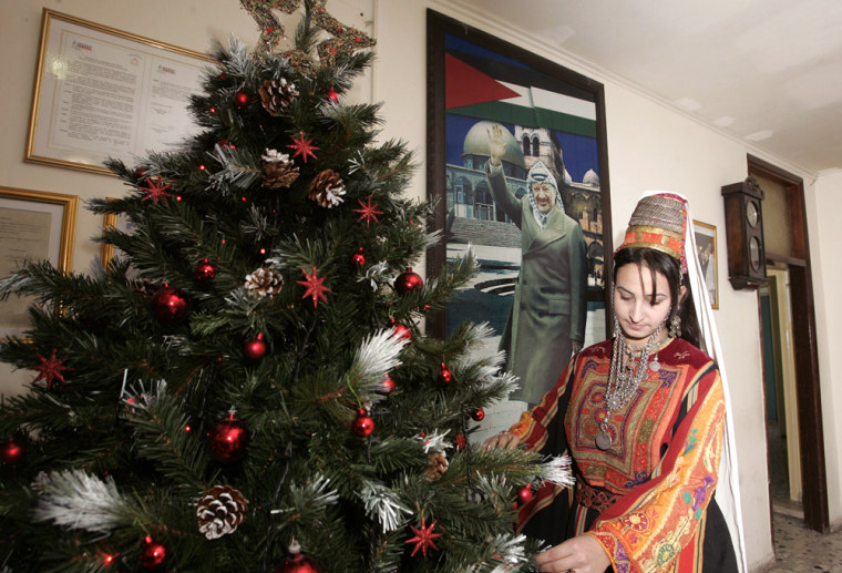Image: A Palestinian woman wearing traditional clothes decorates a Christmas tree inside the municipality building in the West Bank town of Bethlehem