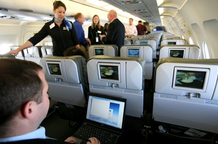 Brad Garlinghouse, left, senior vice president of Yahoo, demonstrates the capabilities of a laptop aboard an Airbus A320 aircraft equipped with a wireless network. JetBlue Airways Corp. began offering free online messaging services on one of its planes, becoming among the first airlines to offer in-flight Internet access.