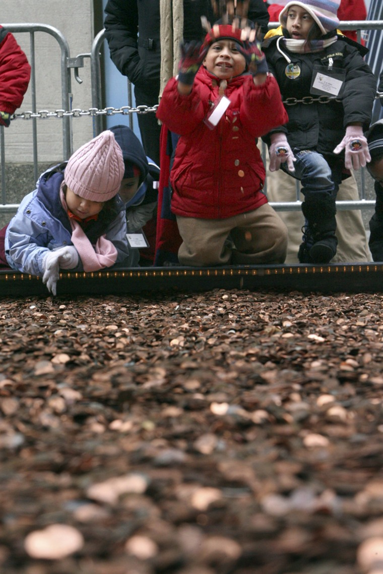 Children who helped collect pennies play with them during a ceremony to unveil the Penny Harvest Field on Monday in New York City.