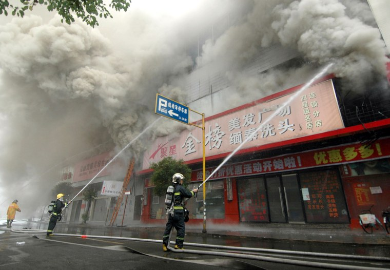 Firefighters battle a blaze at a 28-story building in the eastern commercial city of Wenzhou, China, on Wednesday.