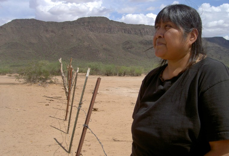 Image: Tribal elder Ofelia Rivas stands at a rusted fence marking the Arizona.-Mexico border on the Tohono O'odham Nation.