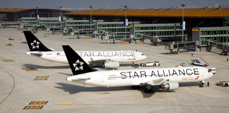 Image: To celebrate their new membership in the Star Alliance, a Shanghai Airlines Boeing 767-300 (foreground) and an Air China Airbus A330-200 painted in the alliance's colors are posed in front of the new Terminal 3 at Beijing Capital International Airp