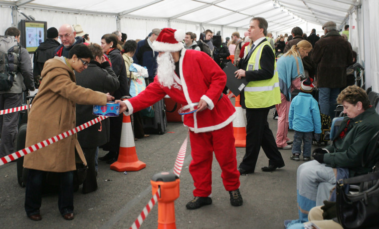 Image: airport staff dressed in a Santa outfit hands out sweets to passengers waiting in a tent