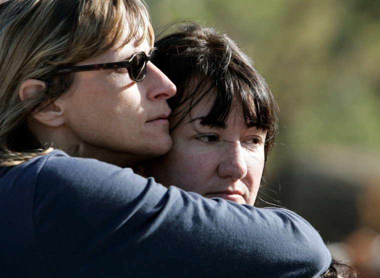 Image: Anne Gurnee, right, who lost her home in the recent wildfires, gets a hug from mentor Debbie Williams