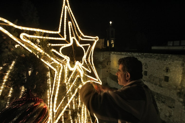 """Image: A Palestinian municipal worker fixes the """"star of Bethlehem"""" on top of the central Christmas tree in Manger Square outside the Church of the Nativity."""
