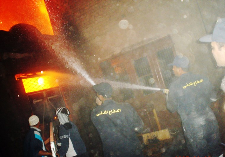 Image: Egyptian firemen attend  a fire set by angry Muslim attackers at shops owned by Coptic Christians