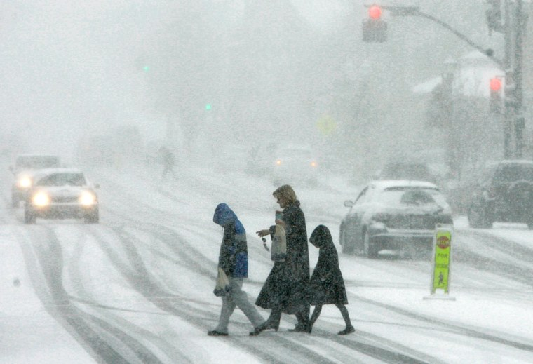 Pedestrians brave the blowing snow as they cross the main street of Chagrin Falls, Ohio on Sunday.