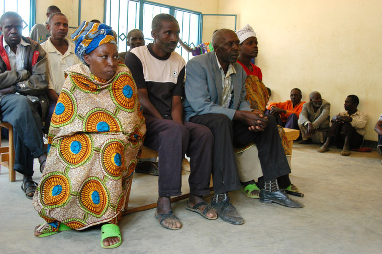 Image: People from Mayange village, in Rwanda, sit and watch during a trial of a gacaca court