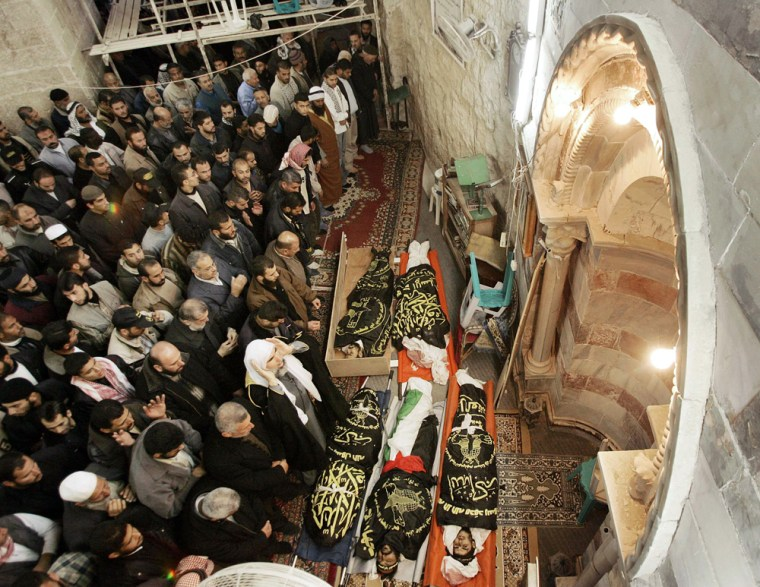 Palestinians pray beside the bodies of Islamic Jihad militants after they were killed by Israeli air strikes in Gaza