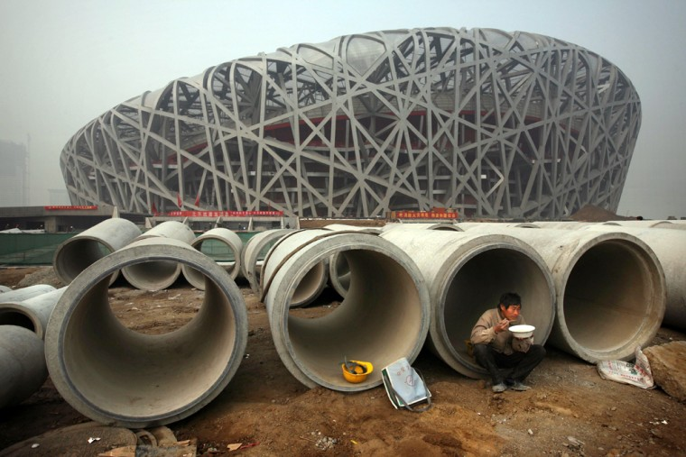 """A Chinese worker eats lunch next to the iconic National Stadium — nicknamed the """"Bird Nest"""" — under construction for the 2008 Beijing Olympic Games, in thisphoto from Nov. 12, 2007."""