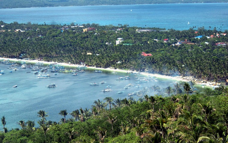 """Image: Boats float off the famous \""""white beach\"""" of the central Philippine island of Boracay"""