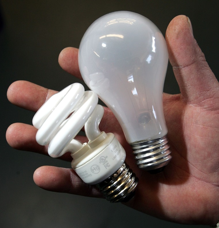 Image: A worker at the City Lights Light Bulb Store holds a traditional incandescent light bulb (R) and an energy efficient compact flourescent bulb