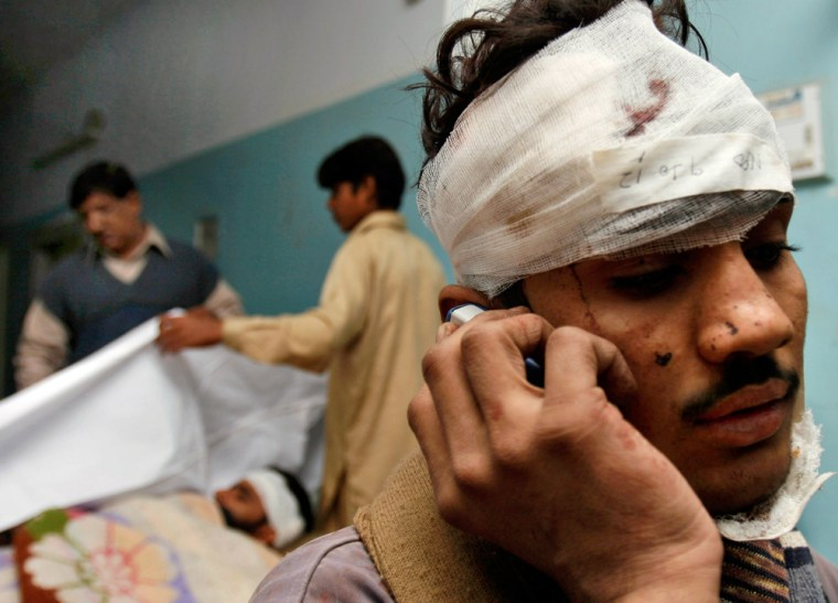 Image: An injured victim of a derailed train talks on his mobile phone at a local hospital in Mehrabpur.