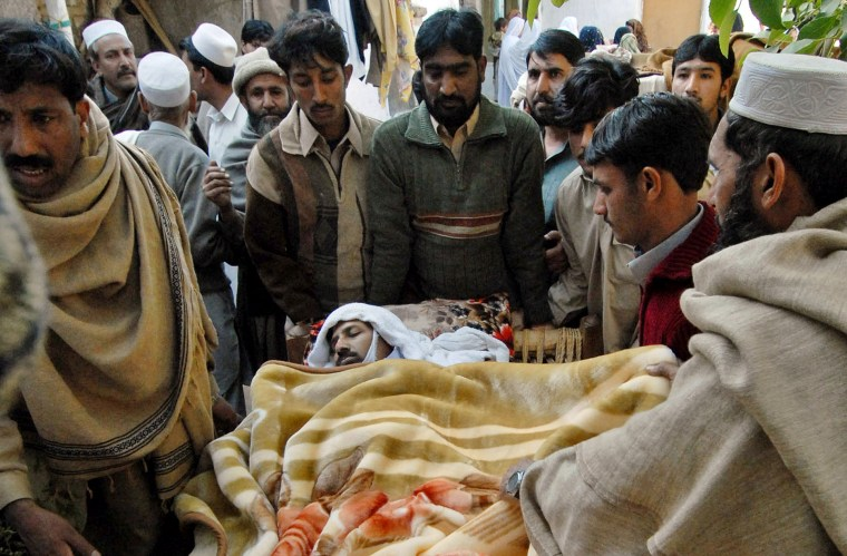 Pakistani villagers carry a man injured in a suicide attack in Sherpao on Friday.