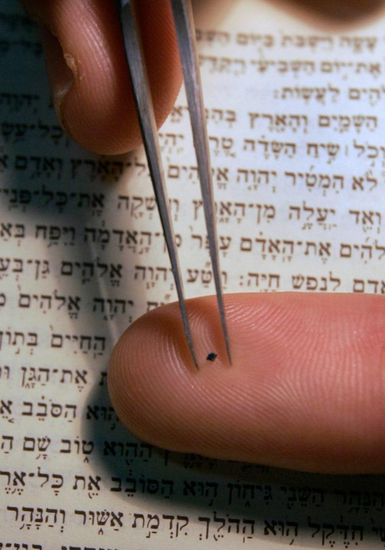 Image: Haifa's Technion University spokesman Ohad Zohar displays a chip containing the entire Hebrew Bible