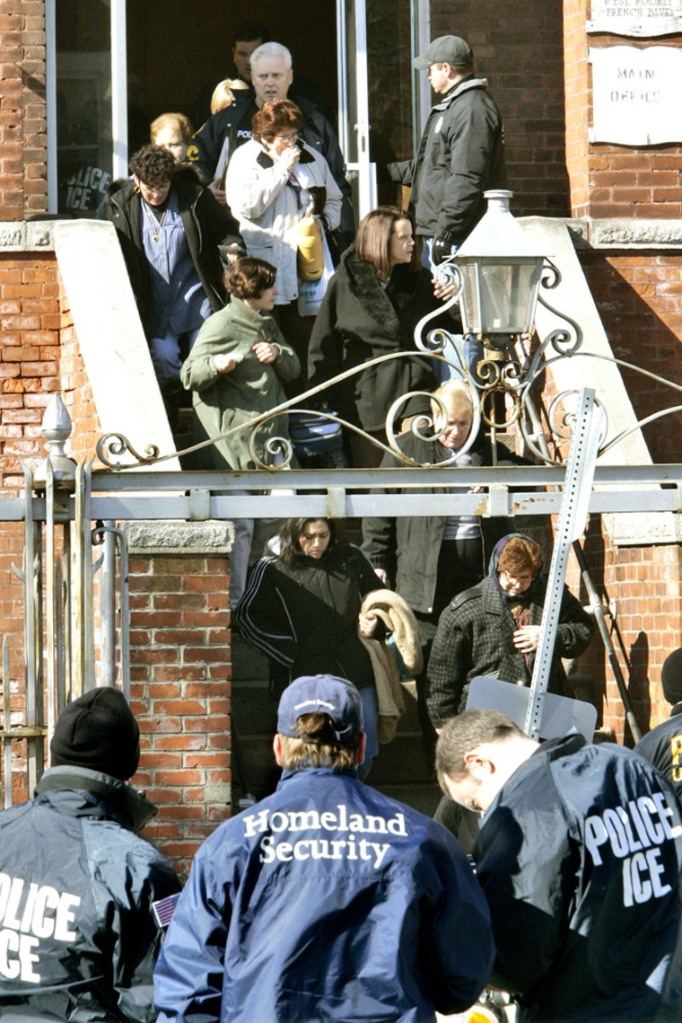 Employees are escorted out after an early-morning raid by federal immigration officials at the Michael Bianco Inc. textile plant in New Bedford, Mass., in March 2007.