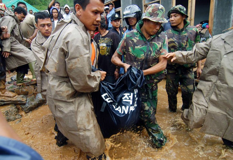 Indonesian soldiers and volunteers wade through waters Wednesdayas they remove a body following a landslide in Tawangmangu, on Java island.