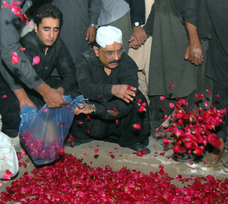 Image: Asif Ali Zardari (R) husband of former Pakistani premier Benazir Bhutto and his son Bilawal (L) shower rose petals on the grave of Bhutto