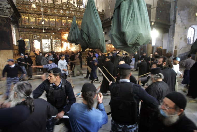 Palestinian policemen try to control a fight that erupted between Greek Orthodox deacons and Armenian priests during the annual cleaning of the Church of the Nativity in the West Bank town of Bethlehem on Thursday.