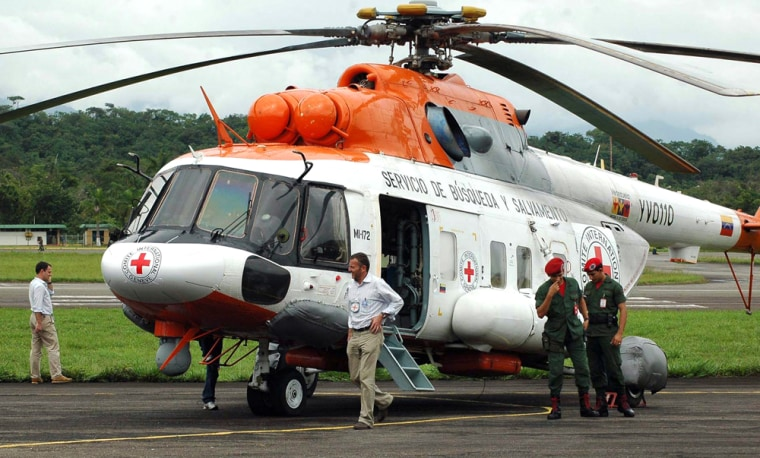 Image: Officials and Venezuelan soldiers stand near an army helicopter with stickers of the Red Cross at the Santo Domingo airport