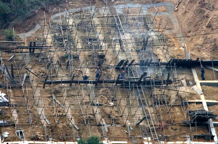 Image: Workers reinforce a hillside along the Yangtze River upstream from the three Gorges Dam