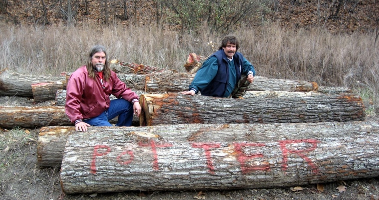 Image:  Dave Potter, left, and his cousin, Mark Combs, sit on fallen white oaks that were allegedly chopped down by a timber thief at the family's property near Whitesburg, Ky.