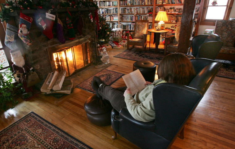 Image: Innkeeper Grace Newman reads a book in front of the fireplace at the Highlands Inn