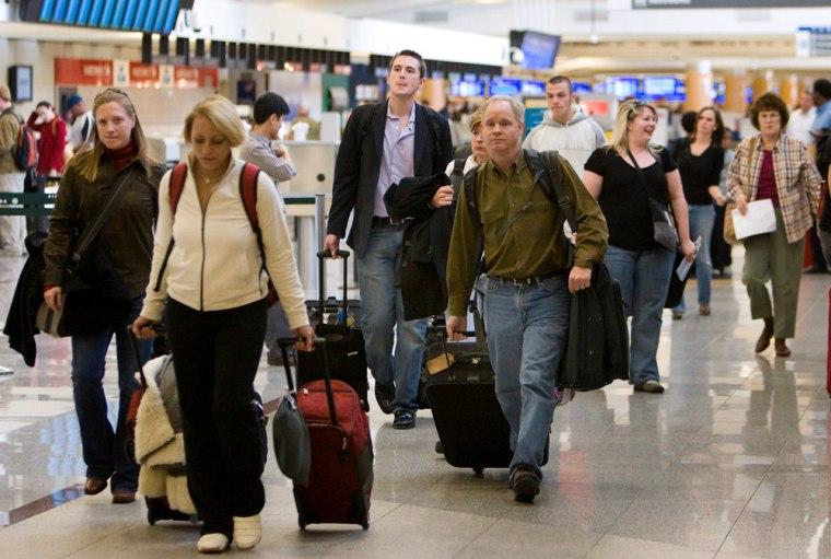 Image:  Passengers pull their luggage through the terminal at Atlanta Hartsfield Jackson International Airport