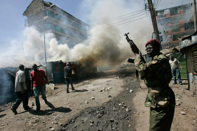 Image: A police officer attempts to secure an area in front off burning buildings in Nairobi, Kenya.