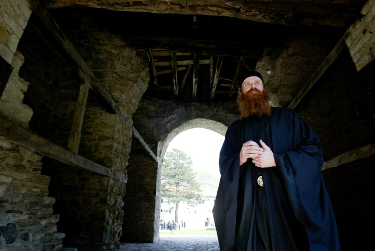 Image: A Serb Orthodox monk stands in the entrance of the Serb Orthodox Monastery of Visoki Decani in western Kosovo