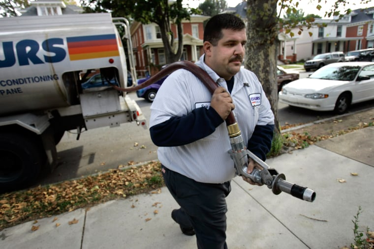 Image: Eric Myer of Eshenaurs Fuels delivers heating fuel to a home in Harrisburg, Pa.