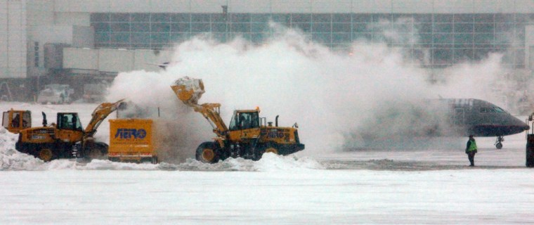 Image: United Express regional jet passes behind a pile of snow as crews clear a Christmas Day winter storm
