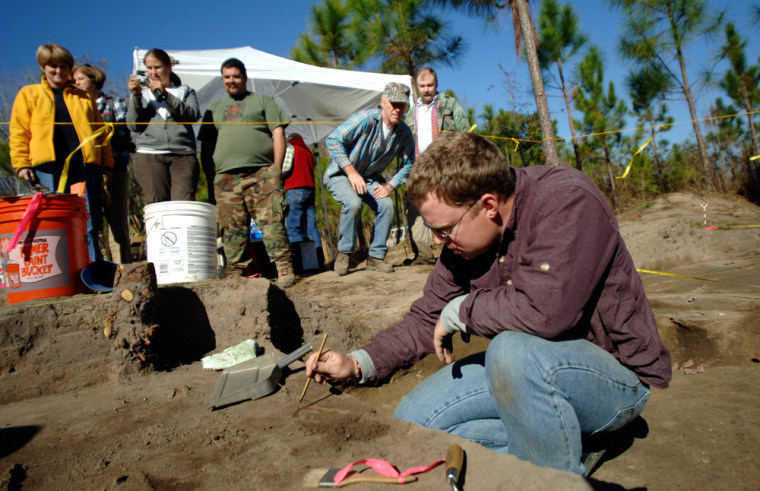 Archaeologist Chad Horton, 28, right, carefully uses a wooden pick to scrape away dirt around a diamond-shaped iron blade found at a site in Jacksonville, Ga. Members from the Fernbank Museum of Natural History in Atlanta believe the site could be part of Hernando de Soto's trail though Georgia in 1540.