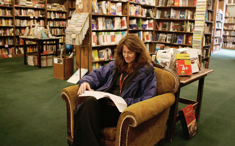Image: Woman reads a book in Powell's bookstore