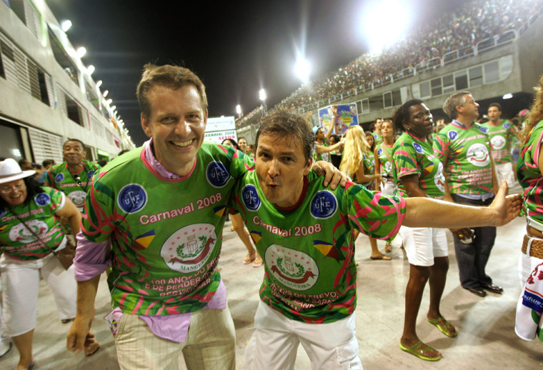 Image: Nicolas, left along with Patrick, right, both from France, participate in the rehearsal of the Mangueira samba school