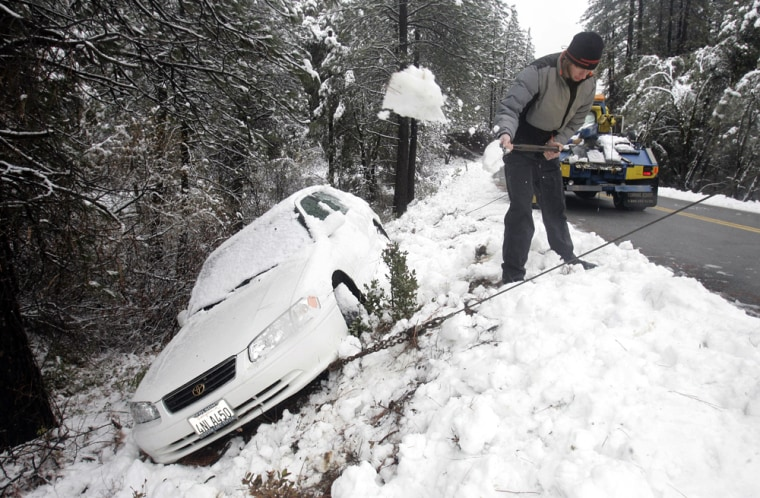 Matthew Harrell digs out his 2000 Toyota Camry on Sunday, as tow trucks prepare to pull the car back onto the road near Gold Run, Calif.