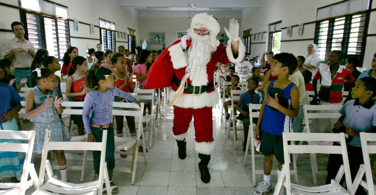 "Image: U.S. cattle farmer John Parke Wright, dressed as Santa Claus, arrives at a church during the ""Three Kings Day"" in a convent in Havana"
