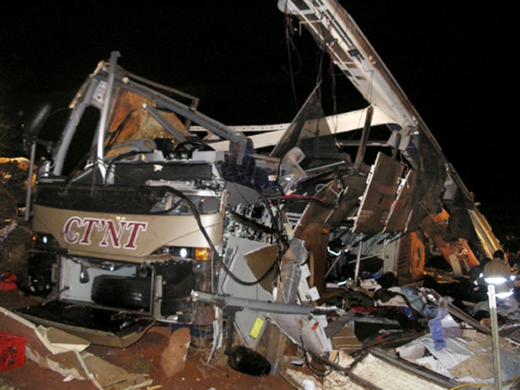 Acharter bus sits crushed after it rolled down an embankment in southeastern Utah on Sunday.