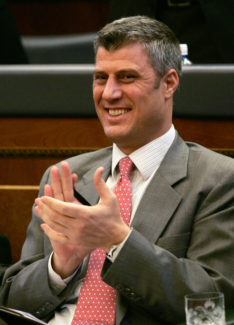Image: Newly elected Kosovo Prime Minister Thaci claps at a session of the Kosovo parliament in Pristina