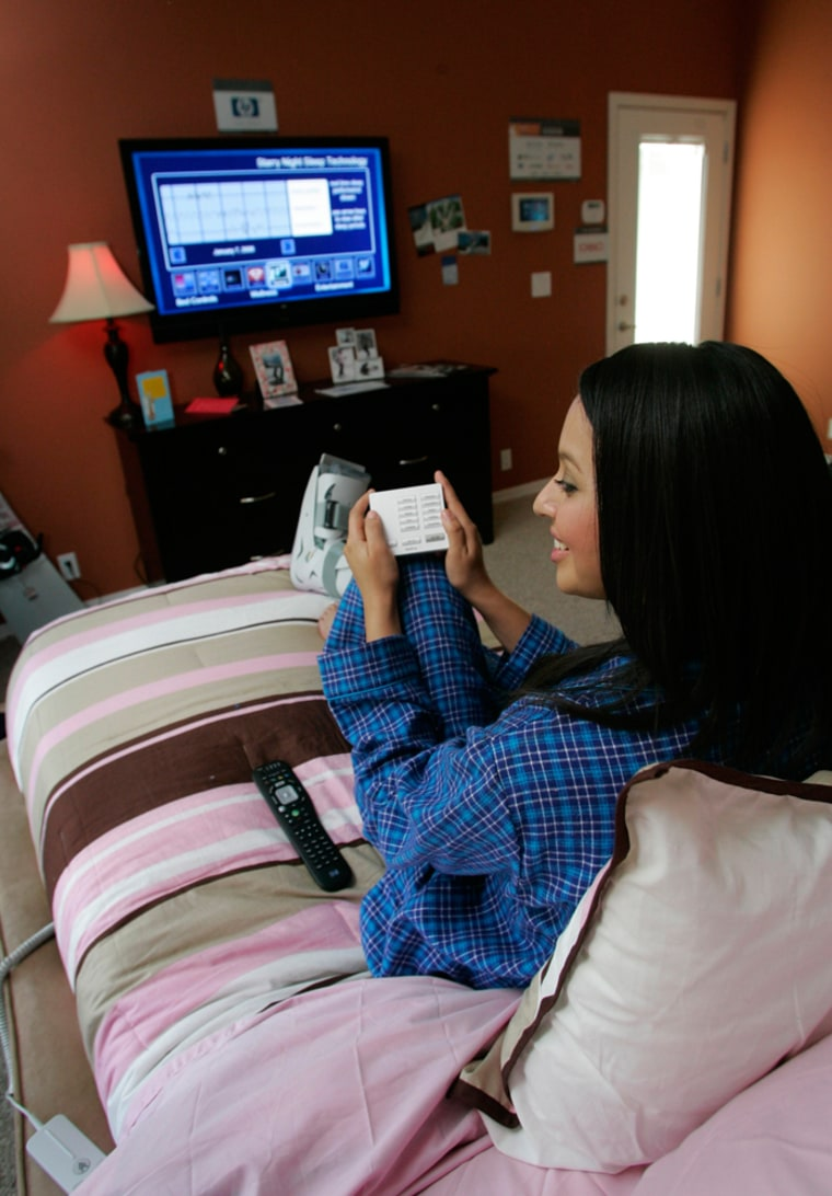 "Image: Model Michelle Rosabal demonstrates the Leggett & Platt ""smart bed"" features in the NextGen Home of the Future during the Consumer Electronics Show in Las Vegas"