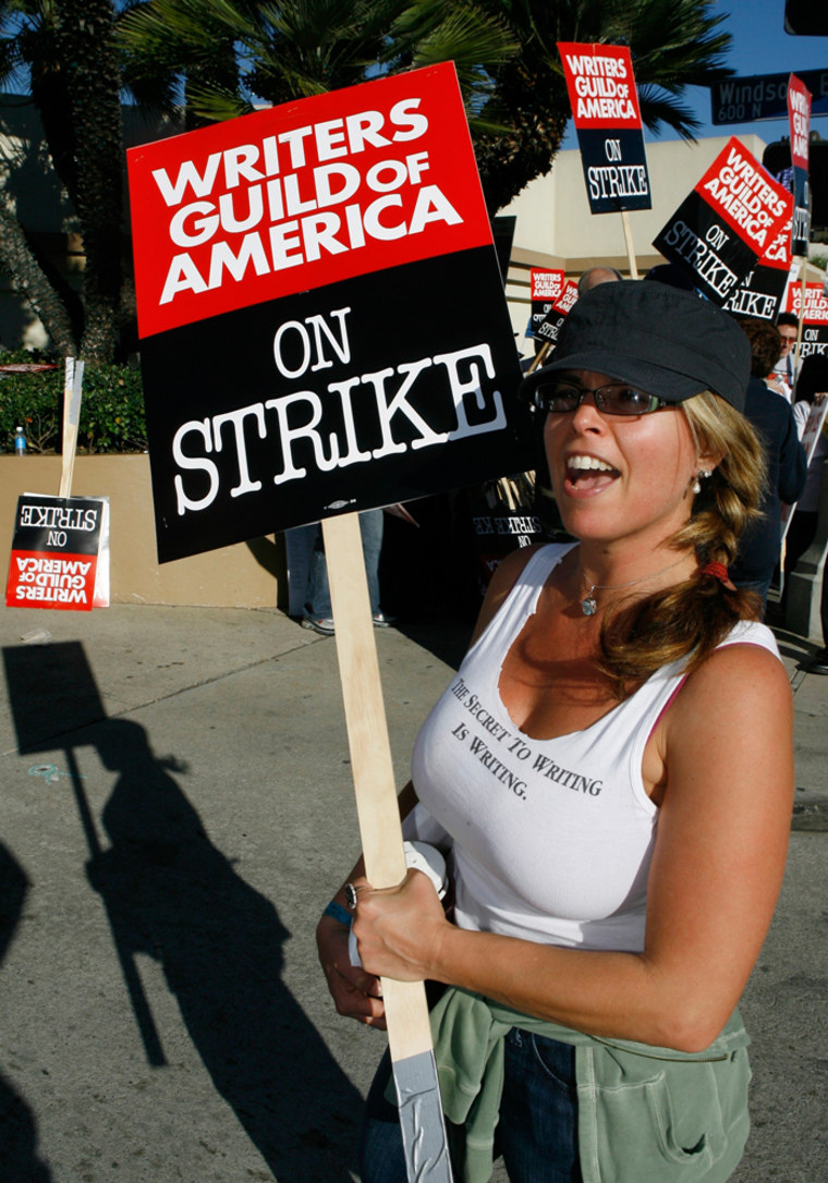 Image: Writer Elizabeth Johnson walks the picket line along members of the Writers Guild of America